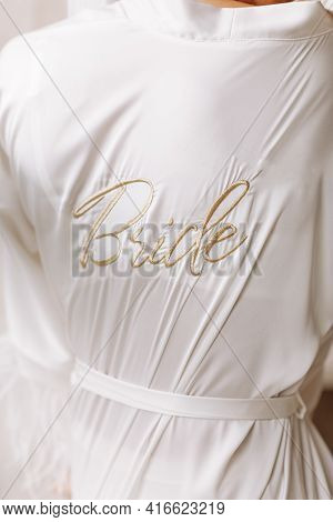 Morning Of Bride. Gorgeous Bride. Beautiful Woman In A White Robe With The Inscription Bride. The Mo