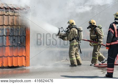 Group Of Firefighters Extinguishing Fire From Fire Hose, Using Firefighting Water-foam Barrel With A