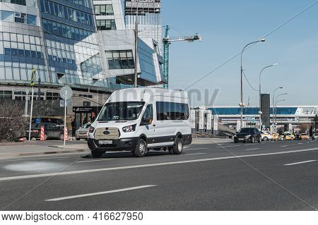 White Ford Van Vehicle On City Road. Fast Moving Car On Moscow Street. Passenger Van Is Fast Transpo