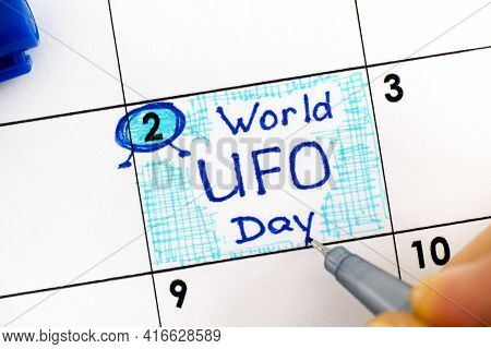 Woman Fingers With Pen Writing Reminder World Ufo Day In Calendar. July 02.