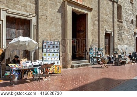 PALMA, SPAIN - APRIL 12, 2019: Street artists sell their paintings in Old Town of Palma - capital and largest city of the Balearic Islands, famous and popular resort and tourist destination.