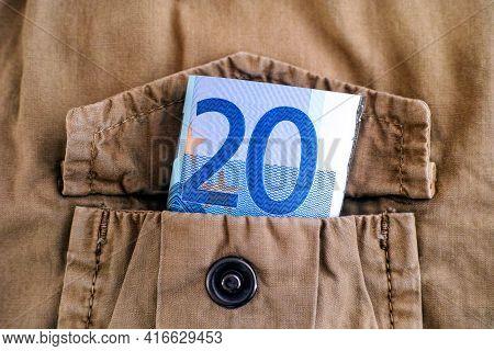 A Twenty Euro Bill In The Pocket Of A Beige Jacket.
