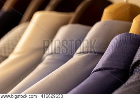 A Portrait Of Variety Of Nice Formal Shirts Hanging From Wooden Cloth Hangers In A Wardrobe Closet.