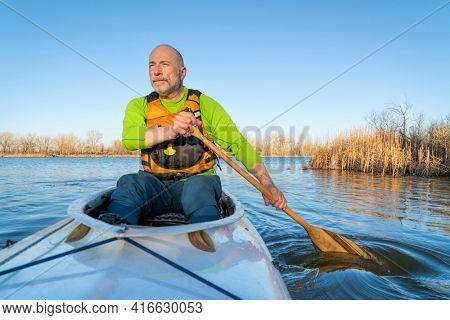 senior male is paddling expedition canoe, early spring scenery on a lake in northern Colorado, POV from boat bow