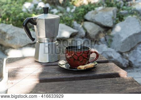 Iron Geyser Coffee Maker And Cup Of Coffee Outside On Old Wooden Table Outside On Summer Day. Active