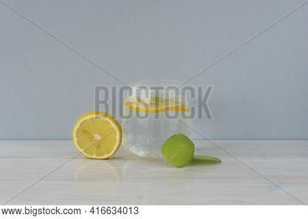 Transparent Glass Of Water, Round Lemon Slice And Mint Leaf On Light Background. Detox Vitamin Refre