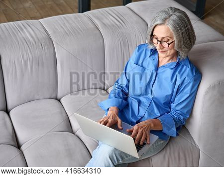 Elder Senior Woman Sitting On Sofa At Home With Laptop. Top Angle Shot Of Modern Grandmother Typing
