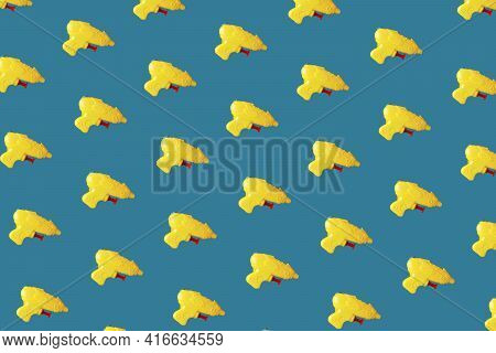 Yellow Plastic Toy Pistols On Blue Background. Minimal Design. Summer Creative Concept