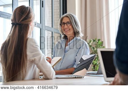 Happy Mature Middle 60s Aged Smiling Lady Boss Manager Teacher Talking To Assistant Or Student Meeti