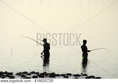 Two Fisherman Silhouette, Myanmar (burma). Amarapura, Near U Bein Bridge.