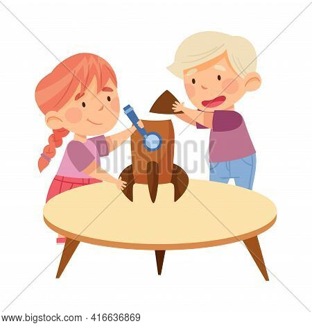Interested Little Boy And Girl At Table Making Rocket Model From Cardboard In Kindergarden Vector Il