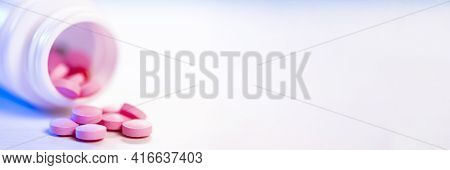 Pink Pills Are Poured From A Plastic Bottle Of Medicine Onto A White Table. Pharmaceutical Industry.