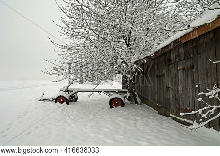 Agricultural Machinery On A Farm Covered With Snow