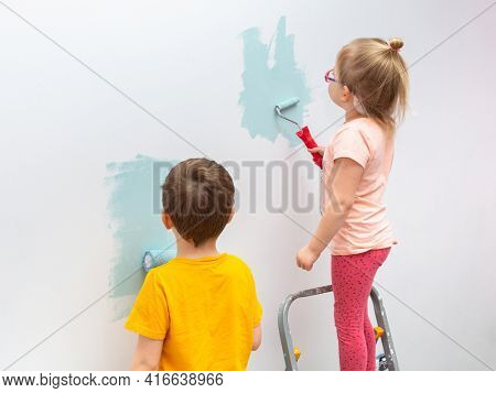 Kids are painting the walls of their room with a roller in turquoise color.