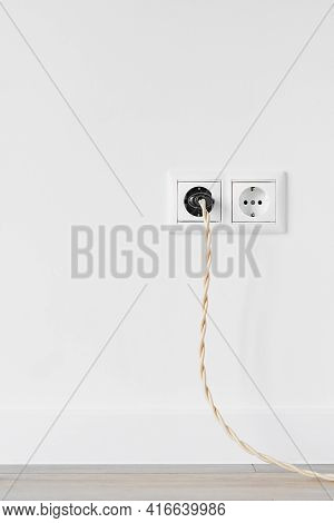 New White Plastic European Electrical Outlet Isolated On White Plastered Wall. An Electrical Plug Wi
