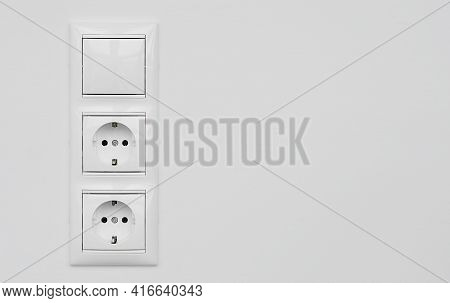 Block Of Two White Plastic Electrical Outlets And A Switch Isolated On A White Plastered Wall. Elect