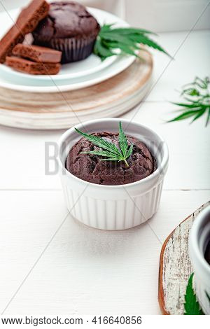 Cooking Weed Muffins In Baking Dish With Cannabis On Top On White Table. Marijuana Chocolate Cupcake