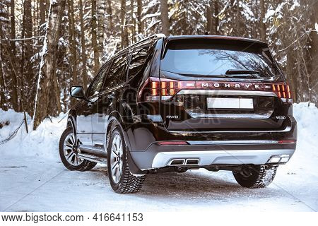 Moscow, Russia - February 15, 2021: Kia Mohave 2021 Black Suv Parked In The Forest In Winter. On The