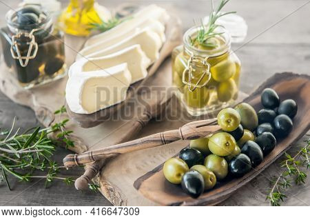 Green And Black Olives In Glass Jars With White Soft Brie Cheese And Young Olives Branch On A Wooden