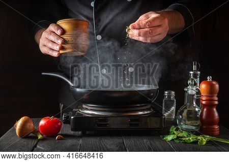 Professional Chef Pours Spices Into Pan. Steam Cooking Hot Food From A Frying Pan. Concept Cooking P