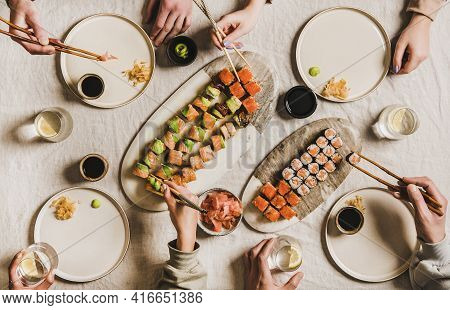 Hands Of People Enjoying Japanese Meal With Sushi At Home