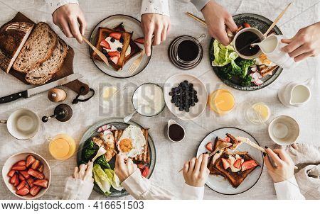 People Having Breakfast With Coffee And Snacks Over White Table