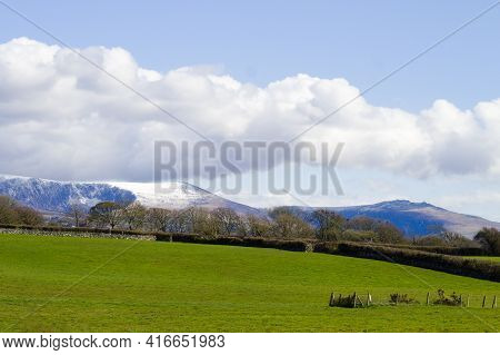 Snowdonia National Park Dramatic Landscape With Gentle Green Fields In The Foreground, And Rugged Sn