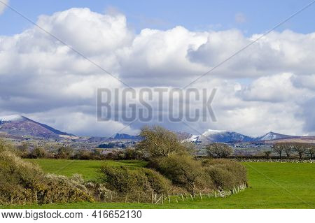 Beautiful Rural North Wales Landscape Green Fields With The Distant Snow Capped Mountains Of The Sno
