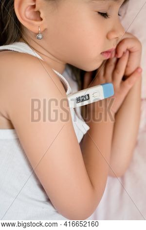 A Child With A Thermometer Lies Sick In His Bed. The Baby Has A High Body Temperature. The Girl Is S