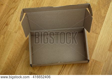 Open Cardboard Box On A Wooden Background. Close Up.