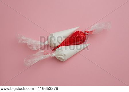 Multicolored Glazing In Icing Bags On A Pink Background.set For Decorating Desserts. Icing For Ginge