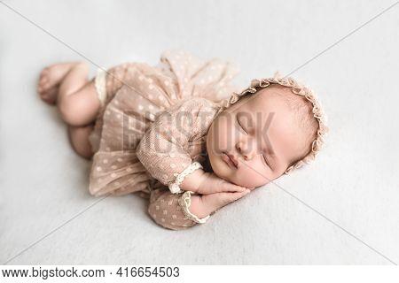 The Newborn Sleeps Sweetly With His Hands Tucked To His Cheeks. Healthy Baby Sleep