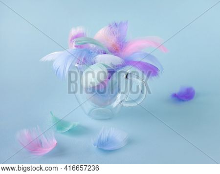 Colorful Pastel Colors Soft Decorative Bird Feathers In A Transparent Glass Glass. Soft Focus