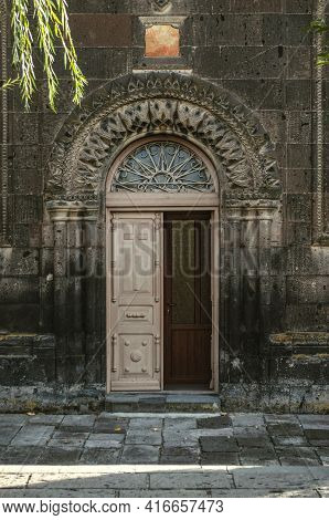Double-leaf Wooden Door With An Oval Glazed Window, With Wrought-iron Bars, Framed By Stone Columns