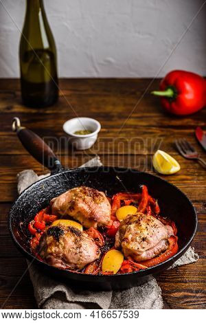Chicken Thighs Baked With Red Bell Peppers, Rosemary And Lemon In Cast Iron Skillet.