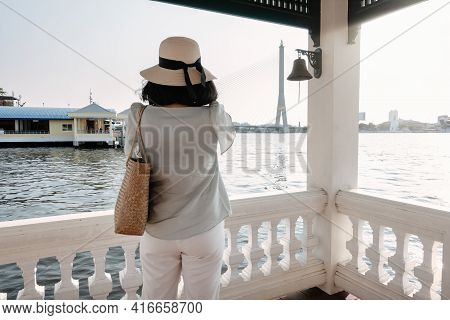 Tourist Woman Having Fun While Sightseeing Bangkok Cityscape Beside The River, Rear View Of Asian To