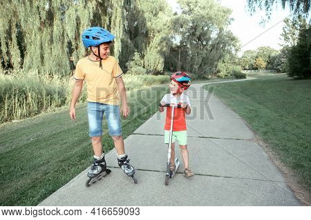 Caucasian Boys Brothers In Helmets Riding Roller Skates And Scooter On Road In Park. Seasonal Outdoo