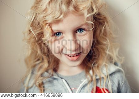 Closeup Portrait Of Beautiful Smiling Caucasian Blonde Girl With Long Hair On Light Neutral Beige Ba