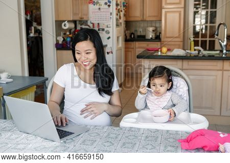 Asian Chinese Pregnant Mother With Daughter Baby Working Online From Home On Internet. Workplace Of