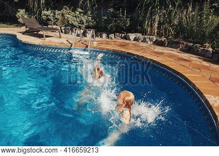Girls Sisters Diving In Water On Home Backyard Pool. Children Siblings Friends Enjoying And Having F