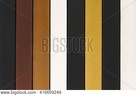 Multicolored Wooden Planks Background. The Backdrop Is Made Of Planks Of Brown, White, Black And Yel