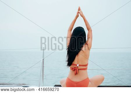 Young Brunette Peaceful And Calm Woman In Orange Bikini Performing Yoga Pose On Boat In Serene Water