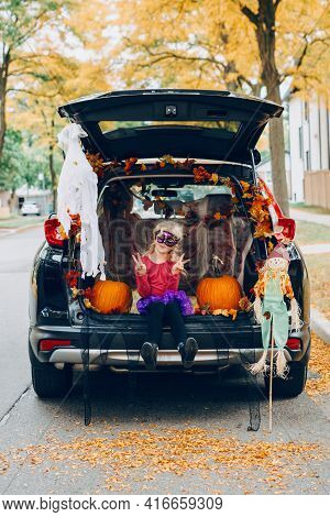Trick Or Trunk. Child Girl Celebrating Halloween In Trunk Of Car. Kid With Red Pumpkins Celebrating