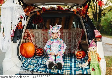 Trick Or Trunk. Sad Upset Baby In Unicorn Costume Celebrating Halloween In Trunk Of A Car. Cute Todd