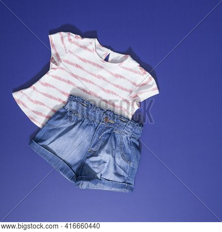 Short Sleeve Blouse And Shorts For Girls; Photo On Blue Background.