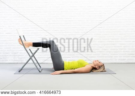Yoga With Props Indoor. Adult Caucasian Woman Lays On The Mat And Put Her Feet On The Chair, Relax D