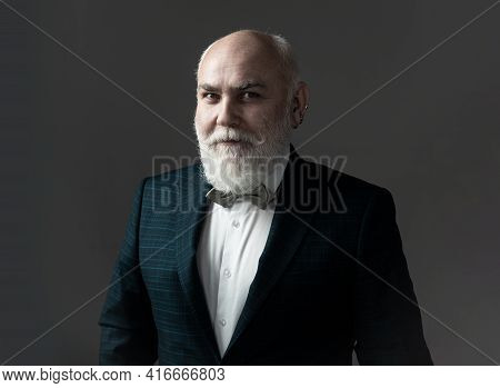 Confident Senior Bearded Man In A Suit And Tie Stand On Gray Isolated Background. Fashion Posing Adu