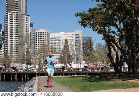Young Athletic Man Running At Urban City Park In San Diego. Full Length Of Healthy Man Running And S