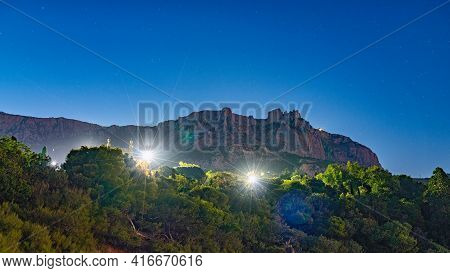 Night Park In The Mountains With Rays From Lanterns. The Walls And Towers Of The Old Palace At Night
