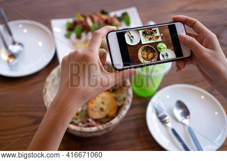The Woman Hand Is Using A Mobile Phone To Take A Picture Of Food On The Dining Table In The Restaura